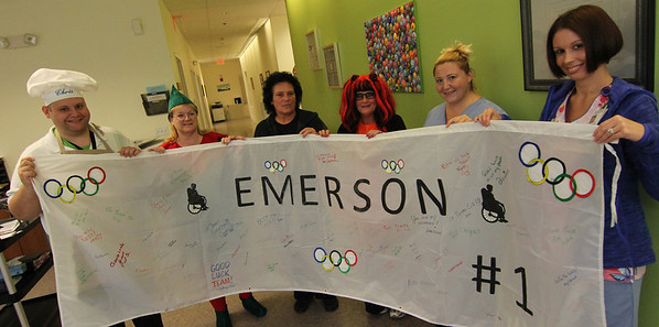 """Allegra Boverman/Gloucester Daily Times. Some of the PACE at Elder Service Plan of the North Shore staff with the Team Emerson spirit banner on Wednesday. PACE at Elder Service Plan of the North Shore site coordinator Diane Wood signs the spirit banner for Team Emerson on Wednesday at the Gloucester center. The team, comprised of about a dozen seniors is going to compete against other North Shore PACE centers in the PACE Olympics, on Thursday at Danvers Indoor Sports in Danvers. The seniors will compete in volleyball, a disc toss at a target, and """"corn hole,"""" a beanbag toss. They have been practicing and training for the last nine weeks. The staff has been working closely with them throughout. From left are: Christopher Frederick, Tanya Munson, Louse Scialdone, JoAnne Frontiero, Johanna Catania and Meg Palazola."""