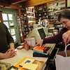 Allegra Boverman/Gloucester Daily Times. Nancy Sullivan of Toad Hall Bookstore in Rockport, right, packs up books that Will Workman, left, of Williston, VT, was purchasing at the store on Wednesday. He and his family are in Rockport for Thanksgiving as they usually are and he always stops into the bookstore to make purchases.