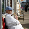 Allegra Boverman/Gloucester Daily Times. Donald Mosher of Rockport enjoys gelato from Sandy's Bay Bakery  a few doors up on Tuesday afternoon on Mount Pleasant Street while seated on a pleasant in front of his daughter Heather Mosher's shop, My Sea Baby.