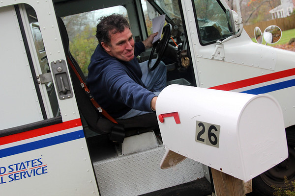 Allegra Boverman/Gloucester Daily Times. Mail carrier Steve Hosker of Essex delivers mail to a home on Pond Street on Tuesday morning.