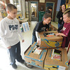 Jim Vaiknoras/Gloucester Times::Left to right:   Sean Brown, Kyle Young, and Aidan Randall load up a dolly with food for The Open Door Food Pantry. Grades K-2 and  Grades 3-5 engaged in a  food drive contest to see which grade levels could collect the most food .The food was collected and transported on Monday morning to Open Door where it will be weighed.  Upon weighing, the winner will be announced at school and the grade levels winner will be awarded a popcorn and movie party.