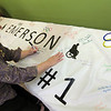 "Allegra Boverman/Gloucester Daily Times. PACE at Elder Service Plan of the North Shore site coordinator Diane Wood signs the spirit banner for Team Emerson on Wednesday at the Gloucester center. The team, comprised of about a dozen seniors is going to compete against other North Shore PACE centers in the PACE Olympics, on Thursday at Danvers Indoor Sports in Danvers. The seniors will compete in volleyball, a disc toss at a target, and ""corn hole,"" a beanbag toss. They have been practicing and training for the last nine weeks."