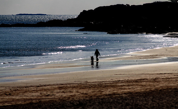 Jim Vaiknoras/Gloucester Times: A woman and her dog walks along the shoreline on Singing Beach in Manchester Monday afternoon.