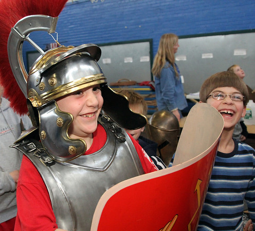 """Allegra Boverman/Gloucestert Daily Times. West Parish student Max Vieira, left, feels what it's like to wear about 50 pounds of Roman armor during """"The Big Fat Science Show"""" held at his school on Wednesday. The show, which is visiting all the Gloucester elementary schools, showcases the great inventions over the ages, from arrowheads to lasers, quill pens to kaleidescopes, motors to chain mail. At right is Derek Ellms."""