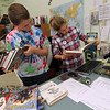 """ALLEGRA BOVERMAN/Staff photo. Gloucester Daily Times. Memorial Elementary School fifth graders Henry Conway, left, and Christina Bullock help check library books back into the school library and then reshelve them on Friday. They participate in the school's new volunteering program, Helpful Hornets started by library teacher Samantha Silag. There are about 80 fourth and fifth graders who participate since the school year started. Some students help out Tuesdays and Thusrdays before school begins, others help out Mondays and Wednesdays after school, and many help out during the lunch periods during the week. They assist teachers and staff with any kinds of tasks needed, on any given day they could be shelving books, wiping down iPads and filing student work, for example. Teachers and staff put out a special sign outside their classrooms and offices indicating they need help. Silag said the kids who participate """"are pumped. They are taking on a leadership role."""" Students had to apply and interview with her and the principal, though they were all accepted, the process was set up to give them that experience, too. They also get a special lanyard to wear when they're working. and they get a special lanyard to wear when they're working."""
