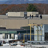 Gloucester: Employees from Varian/Applied Materials watch from the roof top and below as the hub and blades to the windmill are lifted into place Tuesday afternoon in the Blackburn Industrial Park.    Desi Smith/Gloucester Daily Times. November 6, 2012.