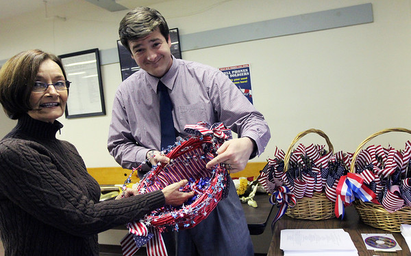 Allegra Boverman/Gloucester Daily Times. From left, Lucia Amero and Richard Barbato of the Office of Veterans Services, are readying for Veteran's Day. They are looking at handmade patriotic ribbon pins made by sisters Donna and Nancy Tulla.