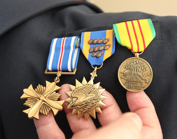 Allegra Boverman/Gloucester Daily Times. Jerry Cook of Manchester, formerlyin the Air Force security service and a retired lieutenant in the Gloucester Police Department, with a few of his medals. From left are his medal for distinguished flying colors, his air medal and his Vietnam service medal.