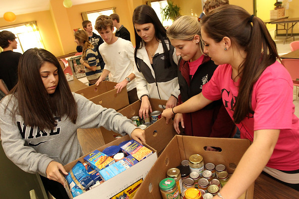 Allegra Boverman/Staff photo. Gloucester High School students from the Interact Club, student council and the National Honor Society were helping to pack up bags and boxes of Thanksgiving foods on Tuesday afternoon at The Open Door Pantry.  From left are: sophomore Julia Jackson, senior Ian Richards, and juniors Taylor Smith, Samantha Ryder and Olivia Legendre.