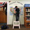 ALLEGRA BOVERMAN/Staff photo. Gloucester Daily Times. Students at Memorial Elementary School in Manchester were participating in a mock Election Day on Friday. First grader Dominic Tiberii, standing high on a stepstool to reach the voting booth, casts his vote for president.