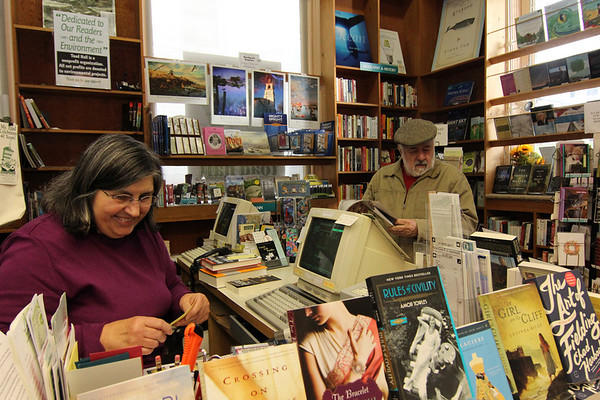 Allegra Boverman/Gloucester Daily Times. Nancy Sullivan of Toad Hall Bookstore in Rockport chats with customer Ray Jenness of Rockport on Wednesday afternoon at the store as she looks up information for a book he wanted to order from her store.