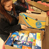 Allegra Boverman/Staff photo. Jesenia Martinez, left, a Gloucester High School sophomore, and Meggie Wambui, a GHS senior, were helping pack up foods for people in need of Thanksgiving meals at The Open Door on Tuesday afternoon.