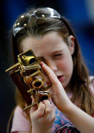 """Allegra Boverman/Gloucestert Daily Times. West Parish Elementary School student Alexia De Coste examines a sextant during """"The Big Fat Science Show"""" held at the school on Wednesday. The show features great inventions from throughout the ages from arrowheads to metal armor, maps to motors, quill pens to kaleidescopes."""