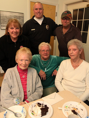 Allegra Boverman/Gloucester Daily Times. Evelyn Hickey, lower left, seated, was celebrating her 90th birthday this past week. Her birthday was actually on Tuesday. Essex Police Chief Peter Silva , standing, center back, heard about her birthday and that she had no real plans for it, and decided to bring her a large cake. Then he learned other residents at Chebacco Terrace where Hickey lives were also celebrating, so it became a party for those with November birthdays. Top row from left are: Janice Farnham, Chief Silva and Peter Landry. Seated bottom from left are Hickey, Nancy Beattie and Fay Platt.