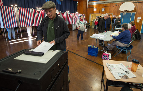 Gloucester:  Bruce Maki places his votes into the ballot machine Tuesday morning at Veterans Memorial School as other voters wait in line to cast theirs.  Desi Smith/Gloucester Daily Times. November 6, 2012.