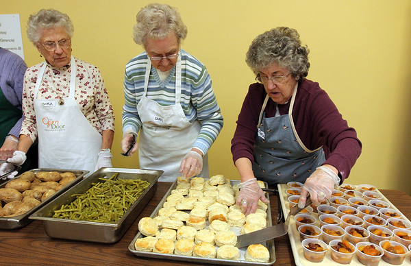 Allegra Boverman/Gloucester Daily Times. From left, preparing to serve a Thanksgiving ham dinner  with all the fixings at The Open Door Pantry with the the St. John's Episcopal Church/Ascension Memorial Church on Tuesday evening are: Moira McLaughlin, Carol Poirier and Charlotte Dodge. They are all from Ipswich and members of the Ascension Memorial Church.