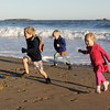 Manchester: From left, Forrester Clark, 4, Malcolm Crawford, 4, and Katalin Clark, 3, run away from the waves at Singing Beach as an offshore storm made for big surf Friday afternoon. Eventually a wave came in too close and got the kids feet wet. Mary Muckenhoupt/Gloucester Daily Times