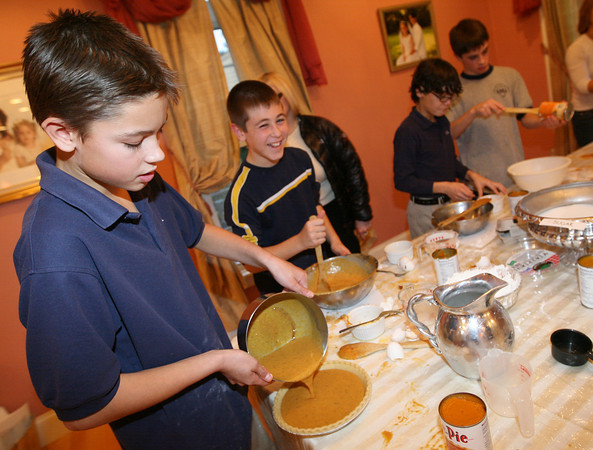Keegan Kolbert of Beverly pours pumpkin pie filling into a crust while Matt Loehle of Georgetown laughs as they and their 7th grade classmates from Saint Mary of the Annunciation School in Danvers bake 40 pies for My Brother's Table in Lynn. Photo by Kate Glass/Gloucester Daily Times