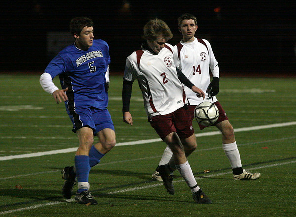 Weymouth: Rockport's Sam Scatterday keeps the ball away from Dover-Sherborn's Chris Flight as teammate Alex Hauck looks on in the state semi-finals at Weymouth High School last night. Photo by Kate Glass/Gloucester Daily Times