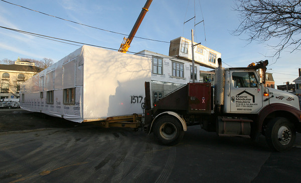 Gloucester: A truck from Maine Modular Haulers backs into the space next to the former Lorraine building with one of the largest units for the new apartment building, which will be four stories high and contain 25 apartments. Photo by Kate Glass/Gloucester Daily Times