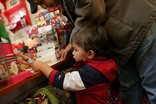 Gloucester: Jack Frontiero hands over his train whistle while buying some toys with his dad John at Toodeloos On Black Friday.  Toodeloos offered 35 percent off from 6 to 8 a.m., 25 percent off from 8 to 10 a.m. and 20 percent off for the rest of the day.  Mary Muckenhoupt/Gloucester Daily Times