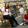 """Essex: Cadyn Hollingsworth and Henry Thurlow listen carefully as librarian April Wanner reads """"One is a Feast for Mouse: A Thanksgiving Tale"""" by Judy Cox during pajama story time at the TOHP Burnham Library on Monday. Photo by Kate Glass/Gloucester Daily Times"""