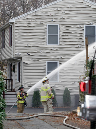 Gloucester: Gloucester Firefighter Jason Lococo hoses down a shed fire behind 206 Washington Street as Deputy Andy McRobb looks on yesterday afternoon. In addition to the shed, the vinyl siding on a nearby home was destroyed. Photo by Kate Glass/Gloucester Daily Times