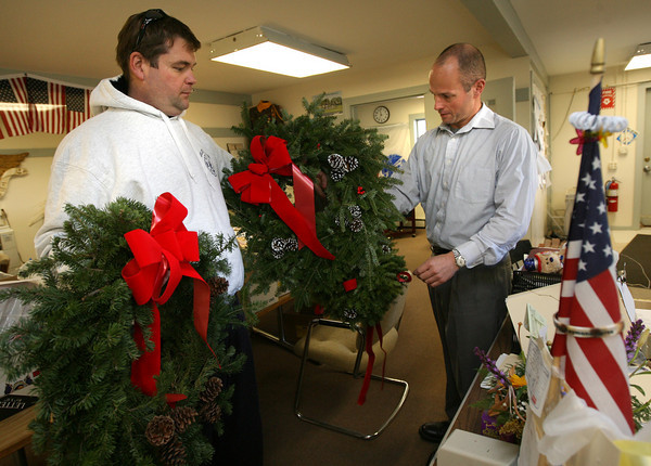 Gloucester: Gloucester Firefighter Jeff Pool hands two wreaths to Jeff Williams, Director of Veterans' Services, to hang around the Veterans' Center. The Gloucester Firefighters Union purchased the wreaths through a fundraiser at the East Gloucester Elementary School. Photo by Kate Glass/Gloucester Daily Times