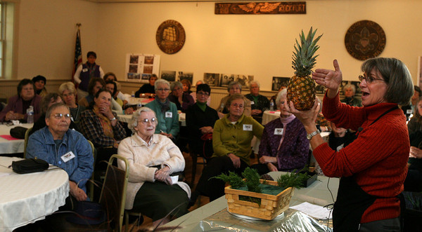 """Rockport: Robin Murphy describes how to dry a pineapple for use in floral arrangements during the Rockport Garden Club's annual meeting at Scout Hall yesterday afternoon. Murphy's presentation was themed """"Home for the Holidays."""" Photo by Kate Glass/Gloucester Daily Times"""