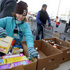 Gloucester: Anna Landgren, 11, organizes boxes of pasta and cereal so they all fit in the banana box while helping out at the Open Door Thanksgiving Food Drive in front of Market Basket Saturday. Also pictured are volunteers Scott Kornusky and hs son Hayden, 7, right. Mary Muckenhoupt/Gloucester Dailey Times
