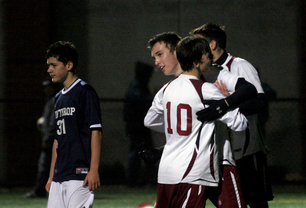 Manchester: Rockport's Shaffy Roell and Nick Scatterday hug teammate Cam Tibert, center, after he scored during their playoff matchup against Winthrop yesterday. The Vikings won 5-1. Photo by Kate Glass/Gloucester Daily Times