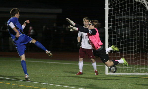 Weymouth: Rockport goalie Keady Segel tries to block Dover-Sherborn's Sam Jordan, but the shot got by to give them a 2-1 overtime win over the Vikings in the state semi-finals at Weymouth High School last night. Photo by Kate Glass/Gloucester Daily Times