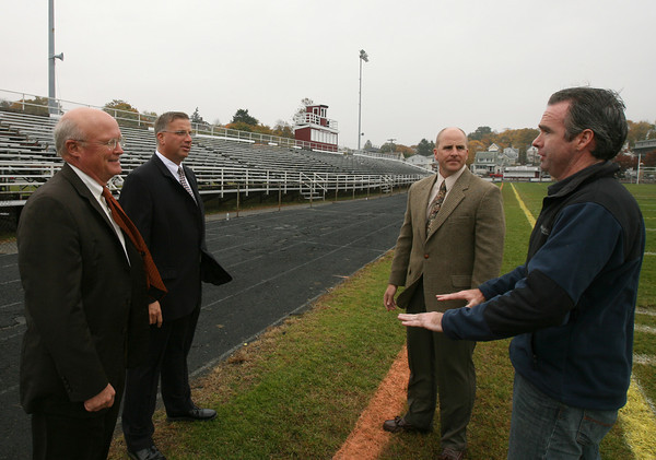 Gloucester: Peter Anderson, President of Rockport National Bank, Mike Luster, Vice President of Commercial Banking, Tim Philpott, GFAA Treasurer, and Mike Carrigan of the Newell Stadium Building Committee, discuss plans to improve the stadium. Rockport National Bank recently donated $10,000 to the Newell Stadium Renewal Project. Photo by Kate Glass/Gloucester Daily Times