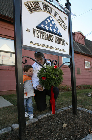Gloucester: Gloucester Firefighter Jeff Pool and his son, Zachary, 2, hang a Christmas ball outside the Veterans Center. The Gloucester Firefighters Union purchased the wreaths through a fundraiser at East Gloucester Elementary School. Photo by Kate Glass/Gloucester Daily Times
