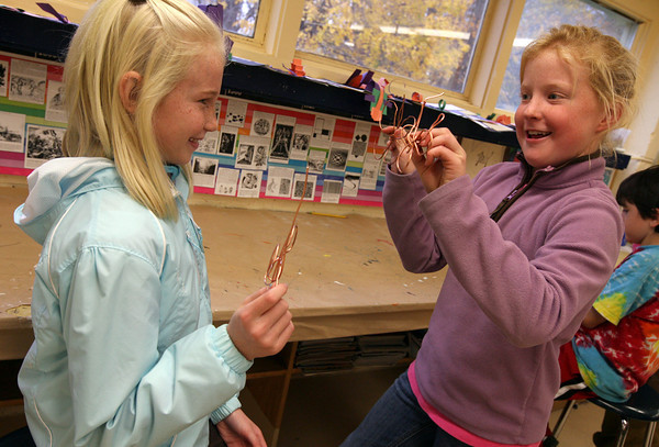 """Essex: Abby Lantz, right, shows her friend, Lily Pulver, the butterfly she made from copper wire during art class at Essex Elementary School. Butterflies made by the fourth graders will be assembled into a large sculpture by Chris Williams and auctioned off in the PTO online auction, which begins Wednesday at  <a href=""""http://www.essexpto.com"""">http://www.essexpto.com</a>. Photo by Kate Glass/Gloucester Daily Times"""