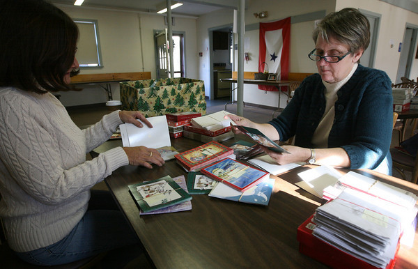 Gloucester: Lucia Amero, left, and Susan Canning sort through holiday cards that will be sent to troops overseas in addition to care packages. Items still needed include single serve coffee, peanut butter packets, toothbrushes and toothpaste. Donations can be dropped off at the Office of Veterans Services on Emerson Avenue. Photo by Kate Glass/Gloucester Daily Times