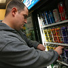 Gloucester: Brian Campbell rearranges the Four Loko display at the Liquor Locker in Gloucester. The state is considering banning the beverage, which contains high amounts of alcohol and caffeine. Photo by Kate Glass/Gloucester Daily Times
