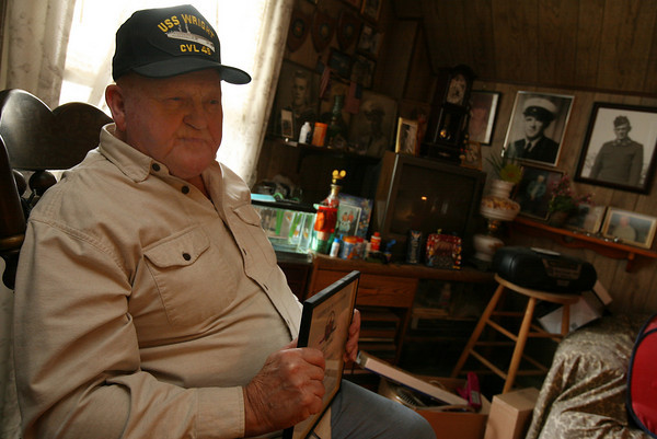 William Haselgard of Gloucester sits in his living room, which is decorated with photos of his brothers, who served in the Army, Navy, and Coast Guard. Haselgard was a member of the Navy from 1952-1976. Photo by Kate Glass/Gloucester Daily Times