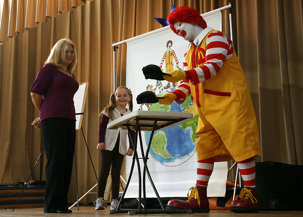"""Gloucester: Andrea Milne, a kindergarten teachers assistant, and Chiara O'Connor, a first grade student, try to guess where Ronald McDonald hid a bully during """"A Friendship Adventure with Ronald McDonald"""" at Veterans Memorial School yesterday morning. The program was sponsored by the local McDonalds restaurant and focused on anti-bullying. Photo by Kate Glass/Gloucester Daily Times"""