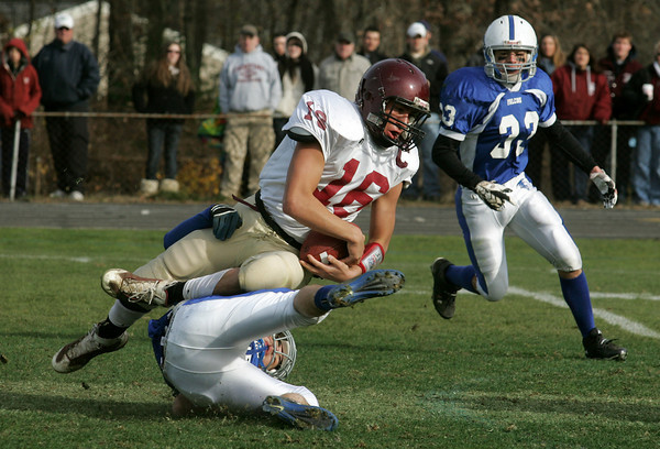 Danvers: Gloucester's Gilbert Brown holds onto the ball after being tackled by Danvers' T.J. Stanley during the Thanksgiving Day football game at Deering Stadium Thursday morning. Gloucester defeated Danvers 43-0. Also pictured is Danvers' Jake Palazola, right.  Mary Muckenhoupt/Glocuester Daily Times