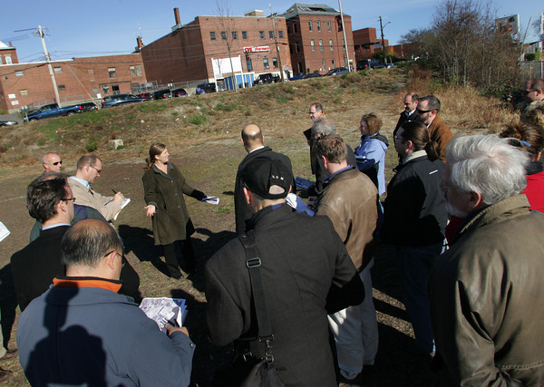 Gloucester:  Gloucester's Community Development Director, standing in the I-4, C-2 lot, gave a tour of the city's planned harbor walk to leading potential developers Friday morning. Mary Muckenhoupt/Gloucester Daily Times
