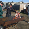 Manchester: Billy Bell salutes as Chaplain Dick Lysiak, left, and First Officer Tom Henderson carry out the ceremonial burning of tattered and torn American flags behind the American Legion yesterday morning as part of the town's Veterans Day ceremony. Photo by Kate Glass/Gloucester Daily Times