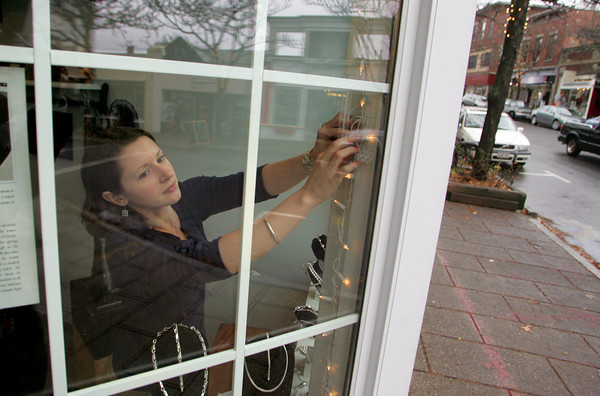 Gloucester: Vanessa Parsons hangs Christmas lights in the window of the Village Silversmith on Main Street Friday.  Parsons said the store had some increased business on Black Friday but that their store in the North Shore Mall had been really busy. Mary Muckenhoupt/Gloucester Daily Times