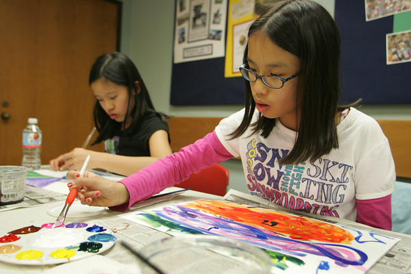 Gloucester: Moriah Murphy-Thornley, 12, right, works on her painting with her sister Shannon, 12, during a visual music program taught by art teacher Claire Wyzenbeek at the Sawyer Free Library Thursday afternoon. The class has students paint while listening to classical music to see what colors and ideas the music brings to their mind and their paint brushes. Mary Muckenhoupt/Gloucester Daily Times