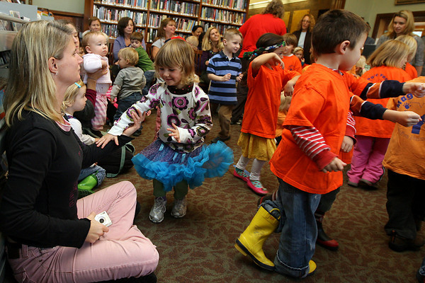 Manchester: Avery Dott reaches for her mother's hand while pretending to drive a car at the Manchester Public Library during a Leeny Tunes Concert on Wednesday morning. Photo by Kate Glass/Gloucester Daily Times