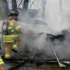 Gloucester: Gloucester Firefighter Jason Lococo moves debris out of the way so his colleagues can get to the source of a shed fire at 206 Washington Street yesterday afternoon. Washington Street was closed for an hour while they extinguished the blaze. Photo by Kate Glass/Gloucester Daily Times
