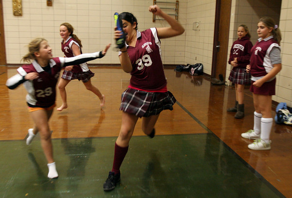 Gloucester: Sabrina Maciel runs away from Rachel Alexander as they play capture the flag in the O'Maley Middle School gym yesterday afternoon. The girls were supposed to have their last field hockey game of the season, but it was cancelled. Photo by Kate Glass/Gloucester Daily Times