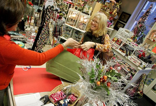 Gloucester: Margaret Ross, right, takes her purchases from Jean Harker as Ross takes advantage of the Black Friday sales at Stone Leaf Friday afternoon. Stone Leaf offered 20 percent off storewide all day Friday making for a steady flow of customers. Mary Muckenhoupt/Gloucester Daily Times