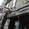 """Manchester: Chris Shea, owner of The Landing in Manchester hangs icicle lights outside the restaurant yesterday afternoon. """"It's good to get in the spirit,"""" he says. Photo by Kate Glass/Gloucester Daily Times"""