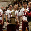 Gloucester:Assistant Football Coach Tom Walsh speaks about the importance of the Kiwanis Trophy as captains Mike Tomaino, Gilbert Brown, Chris Unis, and Andrew Mizzoni stand with the trophy during a pep rally at the Benjamin A. Smith Fieldhouse yesterday morning. Photo by Kate Glass/Gloucester Daily Times